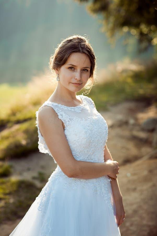 Reizend junge Brunettebraut mit dem natürlichen Make-up, das im sonnigen Wald aufwirft stockfotografie