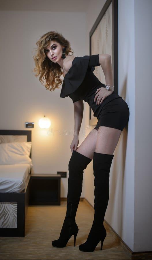 Reizend junge Brunettefrau im festen Sitzkurzschlussschwarzkleid, das an der Wand sich lehnt Sexy herrliches Mädchen mit schwarze lizenzfreie stockfotografie