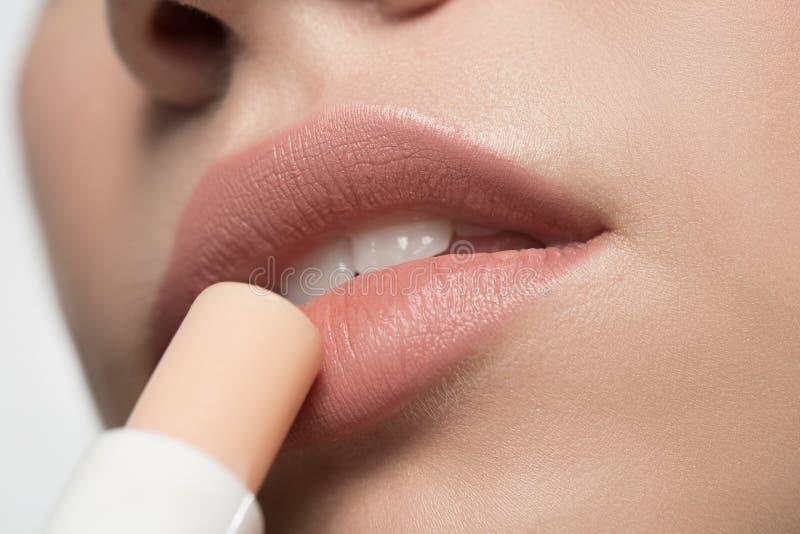 Reizend junge Frau benutzt hypoallergenic Balsam für Lippen stockfotos