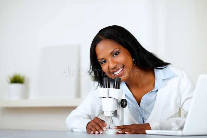 Reizend junge Frau, die ein Mikroskop verwendet stockfoto