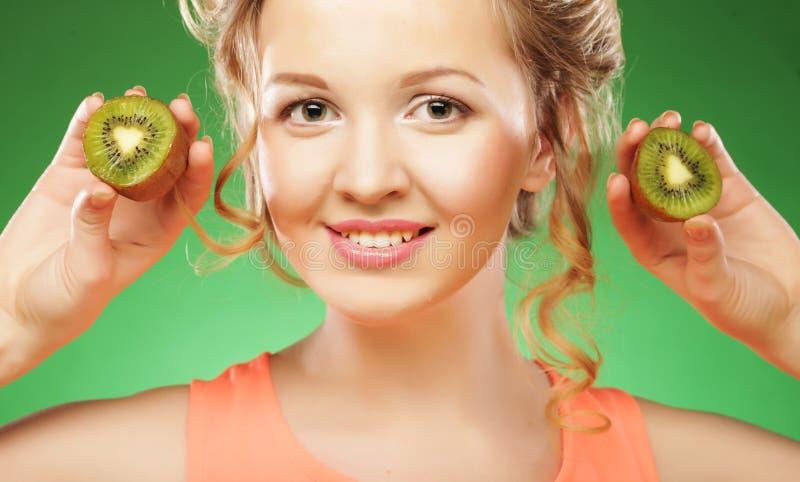 Reizend junge Frau, die frische saftige Kiwi und Lächeln hält lizenzfreie stockbilder