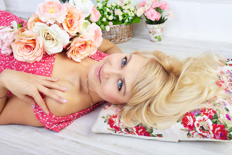 Reizend junge Frau, die mit Blumen auf Kissen aufwirft lizenzfreie stockfotografie