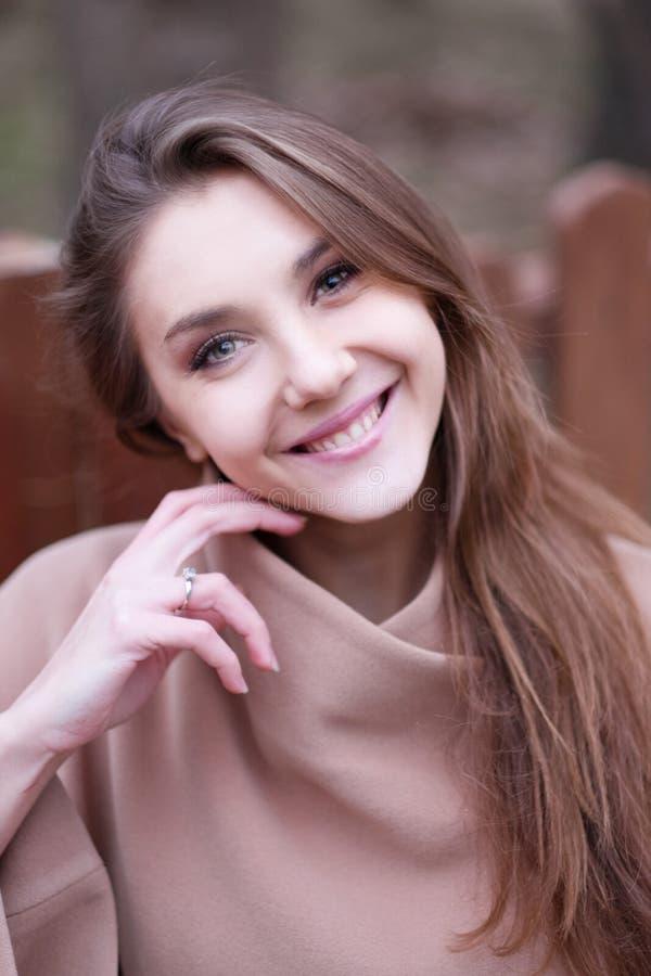 Reizend junge Frau mit dem langen braunen Haar in einem beige Mantel stockfoto