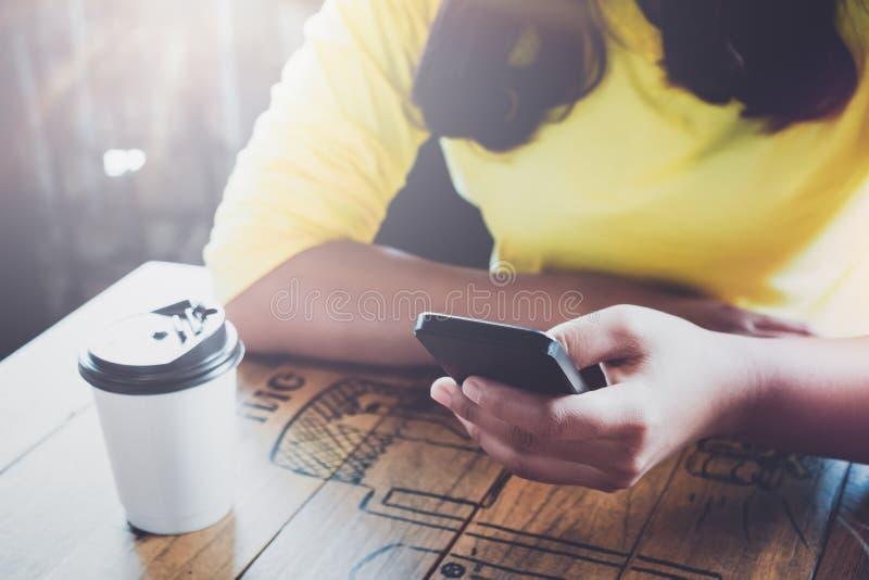 Reizend junge Hippie-Mädchenhände mit an ihrem intelligenten Telefon, das am Holztisch in einer Kaffeestube sitzt lizenzfreie stockfotos