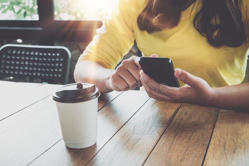 Reizend junge Hippie-Mädchenhände mit an ihrem intelligenten Telefon, das am Holztisch in einer Kaffeestube sitzt lizenzfreies stockfoto