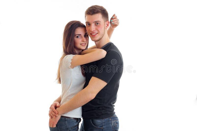 Reizend junger Kerl ist lächelnde Blicke nach rechts und schönes Mädchen umarmend lizenzfreie stockfotografie