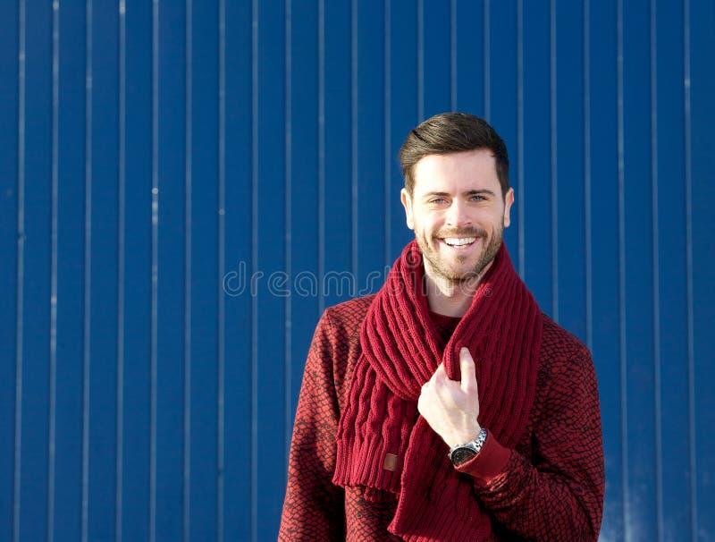 Reizend junger Mann, der draußen Wollschal lächelt und hält lizenzfreies stockfoto