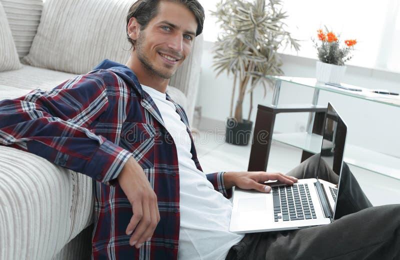 Reizend junger Mann mit dem Laptop, der im modernen Wohnzimmer sitzt lizenzfreie stockfotos