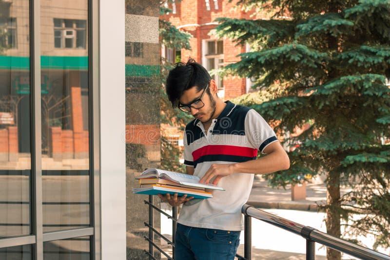 Reizend junger Student mit Gläsern steht in der Straße lizenzfreie stockfotos