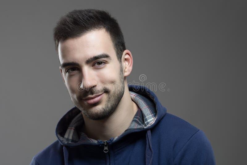 Reizend junger unrasierter Mann, der an der Kamera lächelt lizenzfreie stockfotografie