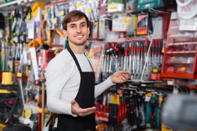 Reizend junger Verkäufer im Schutzblech mit Werkzeugen stockbilder