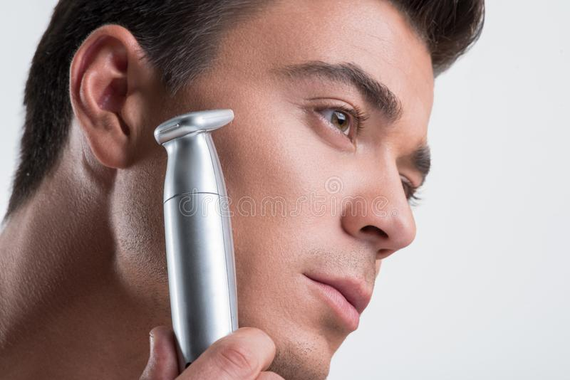 Reizend Kerl hält elektrisches Rasiermesser lizenzfreie stockbilder