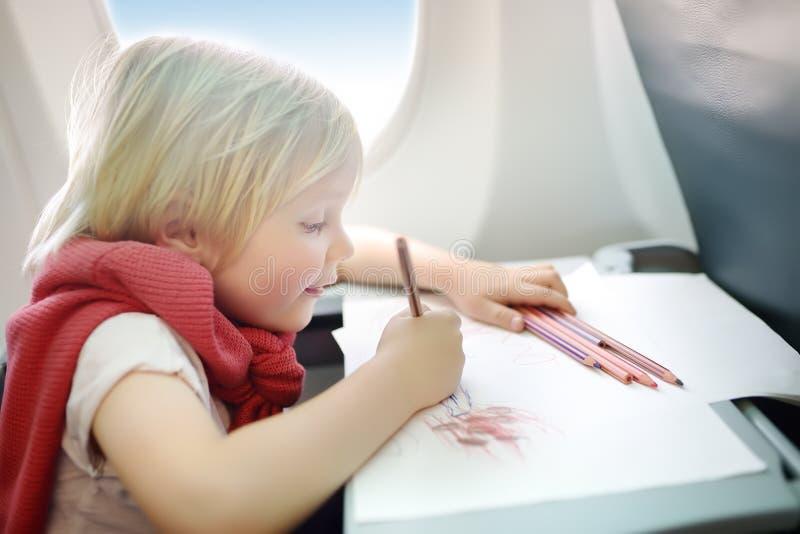 Reizend Kind, das durch ein Flugzeug reist Froher kleiner Junge, der durch Flugzeugfenster w?hrend des Fluges sitzt lizenzfreie stockbilder