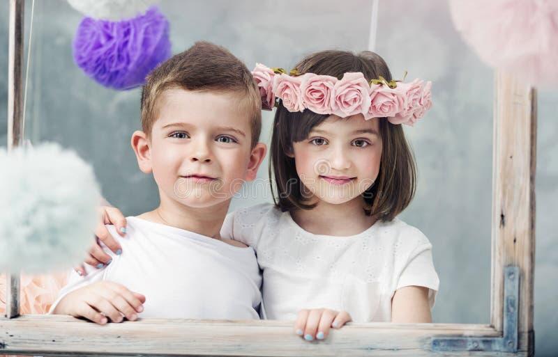 Reizend kleine Kinder, die zusammen aufwerfen stockfoto