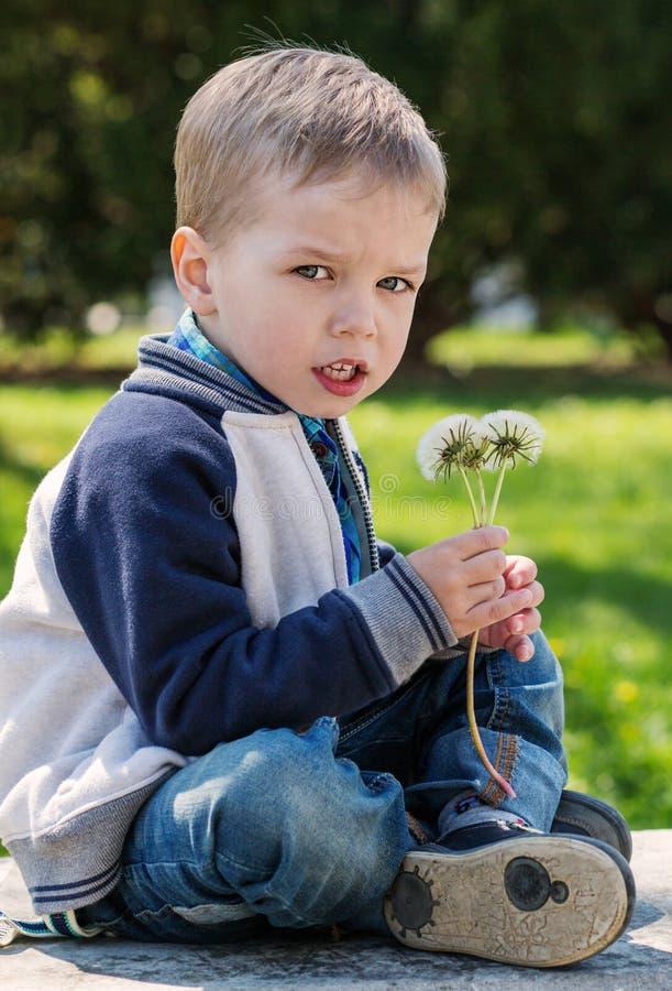 Reizend kleiner Junge mit einem Blumenstrauß lizenzfreies stockbild