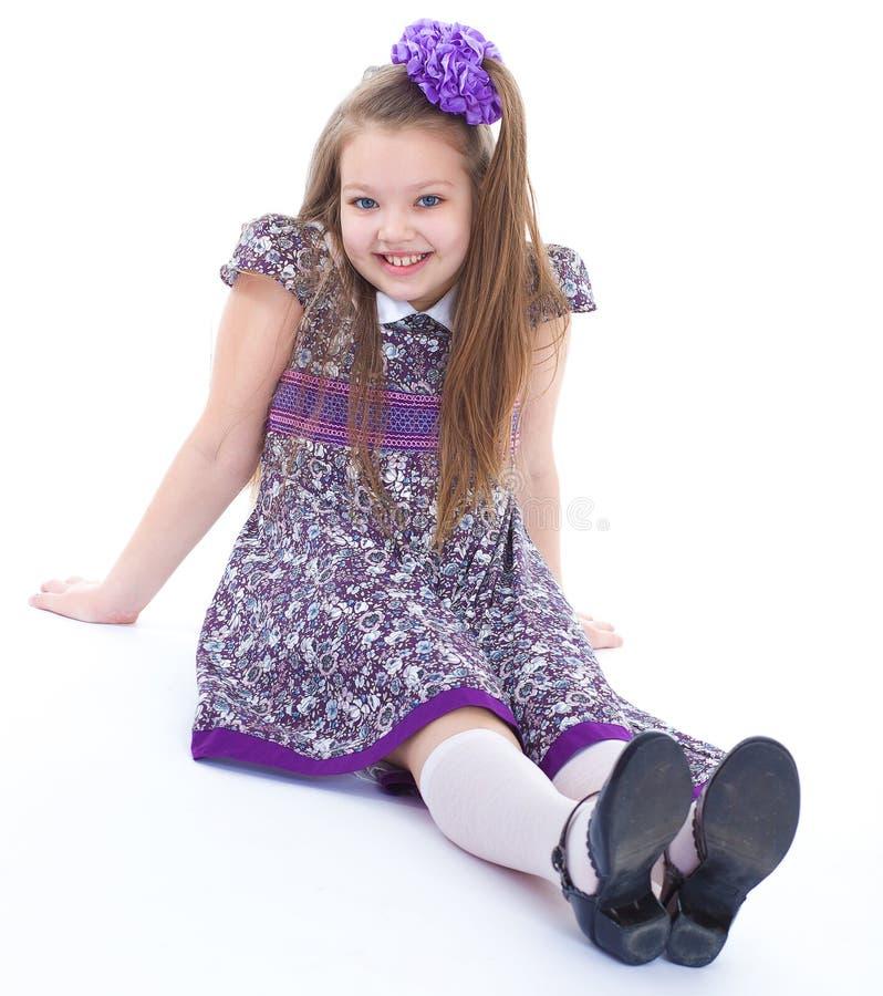 Reizend kleines Mädchen, das auf dem Boden sitzt. stockfotografie