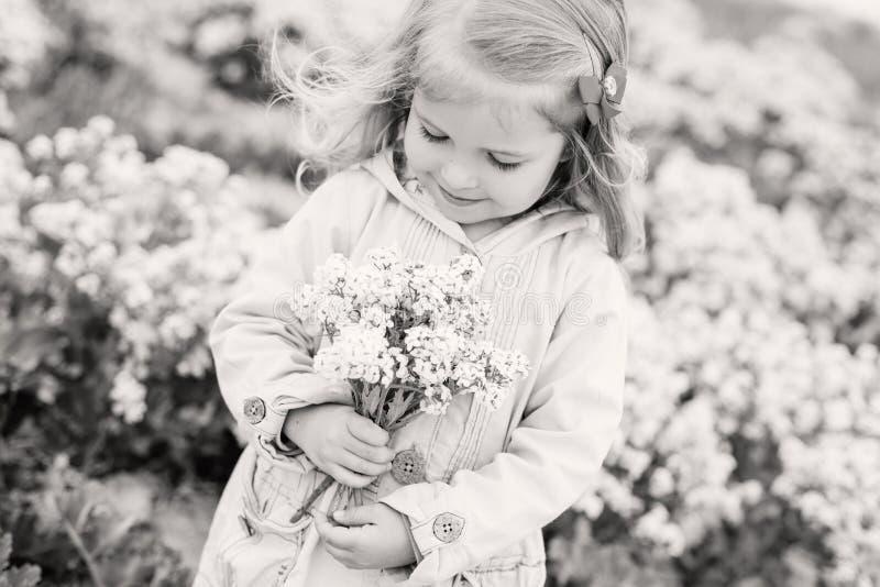 Reizend kleines Mädchen, das einen Blumenstrauß riecht lizenzfreie stockfotografie