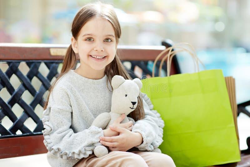 Reizend kleines Mädchen mit Taschen und Spielzeug stockbild