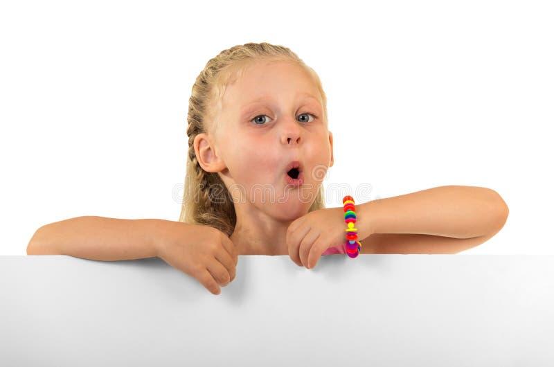 Reizend kleines Mädchen steht hinter einem leeren Brett, lokalisiert auf Weiß stockfotografie