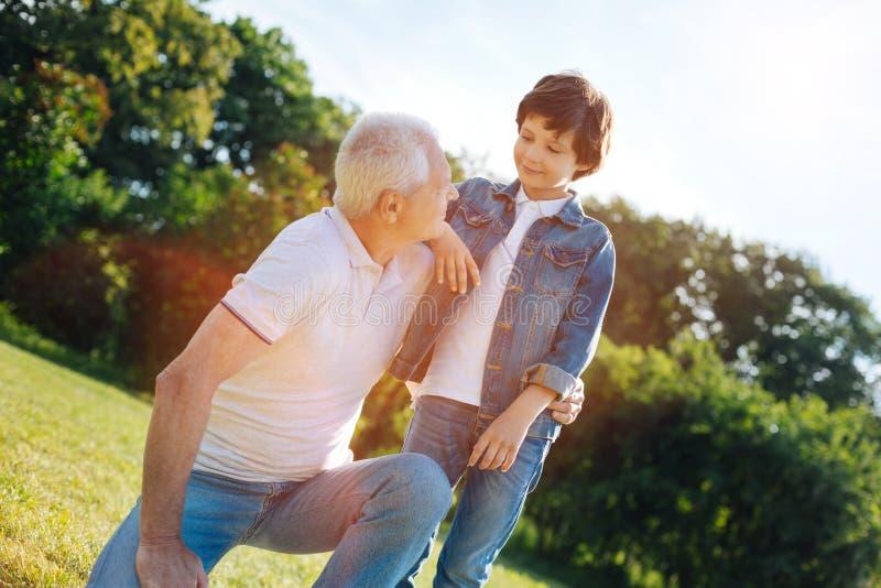Reizend kluger Mann, der mit seinem Enkel spricht lizenzfreies stockbild