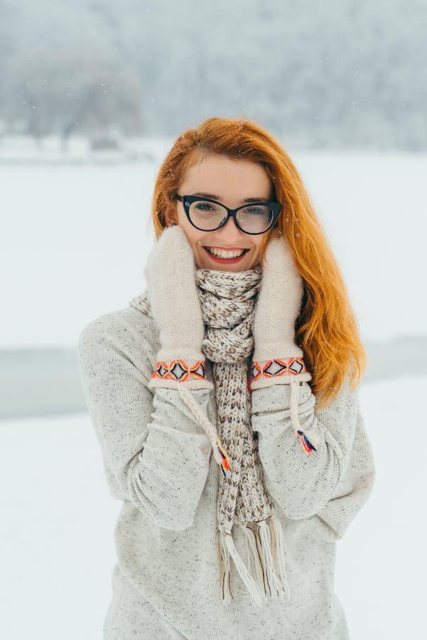 Reizend Lächeln der schönen jungen Frau mit roten tragenden Hauptgläsern, Handschuhen und Schal während der Schneefälle in stockbilder