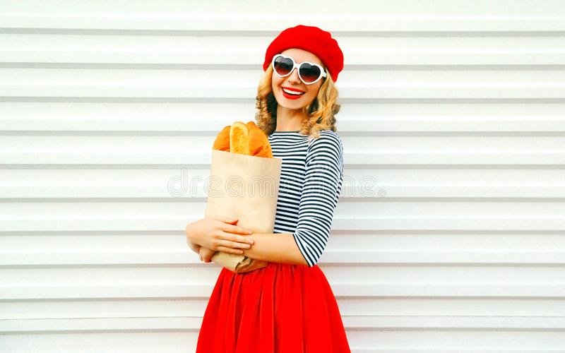 Reizend lächelnde Frau des Porträts, die französische rote Barettholdingpapiertüte mit langem Weißbrotstangenbrot auf Weiß trägt lizenzfreie stockbilder