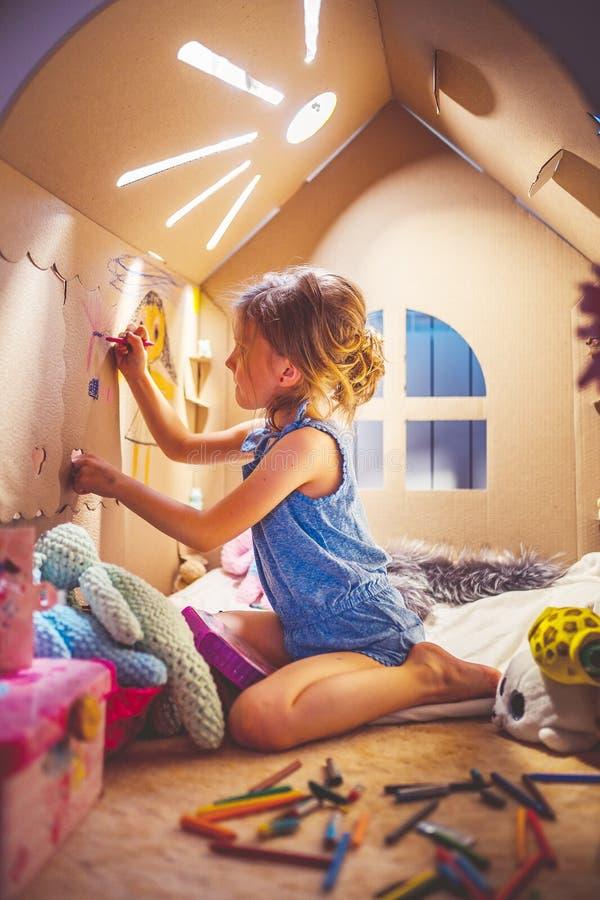Reizend Mädchen, das im Spielzeughaus spielt stockfotografie