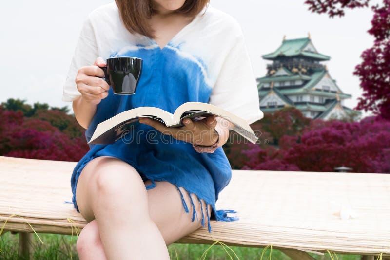 Reizend Mädchensitzen- und -lesebuch Osaka-Schlosshintergrund lizenzfreie stockfotografie