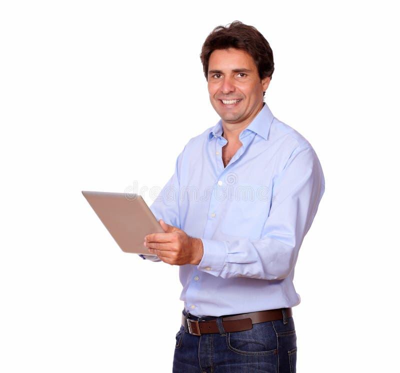 Reizend männlicher Erwachsener, der an Tabletten-PC arbeitet lizenzfreies stockbild