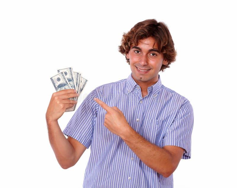 Reizend Mann, der auf Bargelddollar lächelt und zeigt. lizenzfreie stockbilder