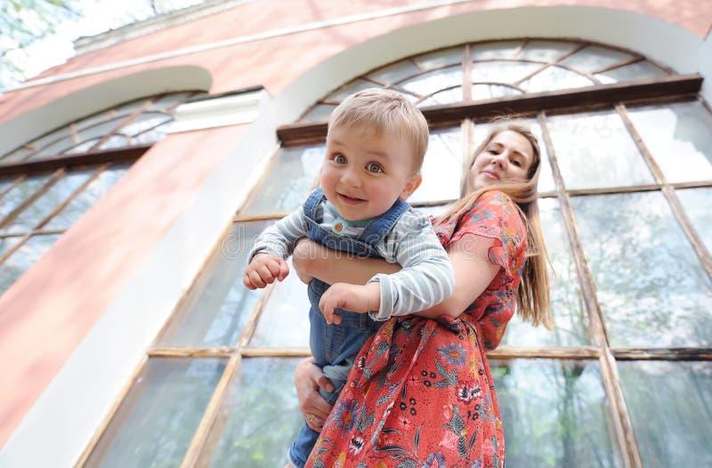 Reizend Mutter und nett ihr Sohn vor dem hintergrund einer großen Glasfassade stockbild