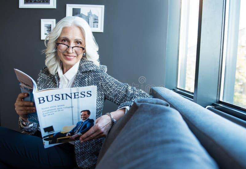 Reizend optimistische stilvolle Dame liegt bei der Zeitschrift stockfotos