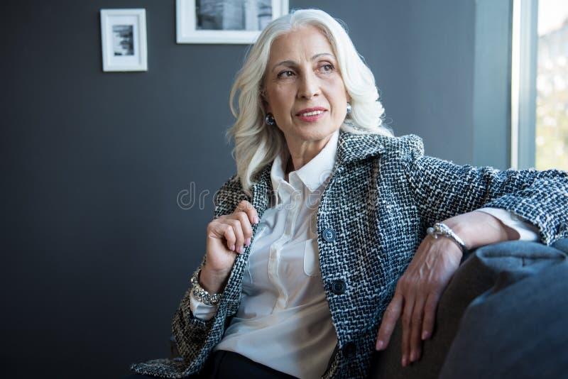 Reizend positive ältere Frau ist auf Sofa entspannend stockfoto
