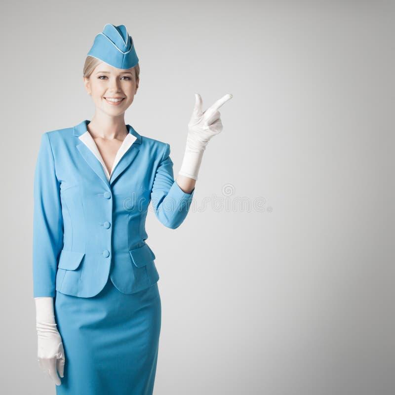 Reizend Stewardess In Blue Uniform, das den Finger zeigt stockfotos