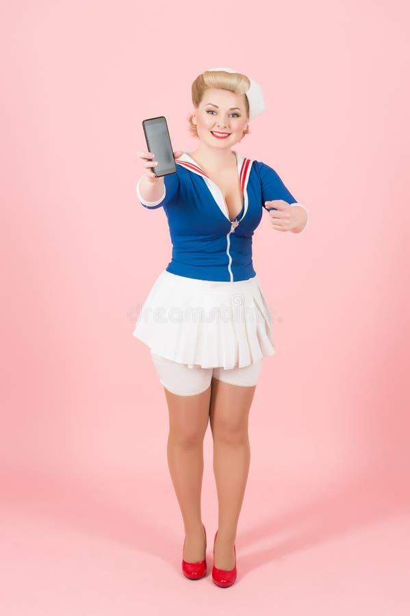 Reizend stilvolle Seemannfrau, die schwarzen Touch Screen des intelligenten Telefons zur Kamera zeigt und mit dem Finger auf Gerä lizenzfreie stockfotografie