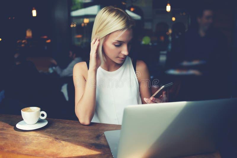 Reizend Studentin, die Zelltelefon und Laptop-Computer während des Restes in der Kaffeestube verwendet stockfotografie