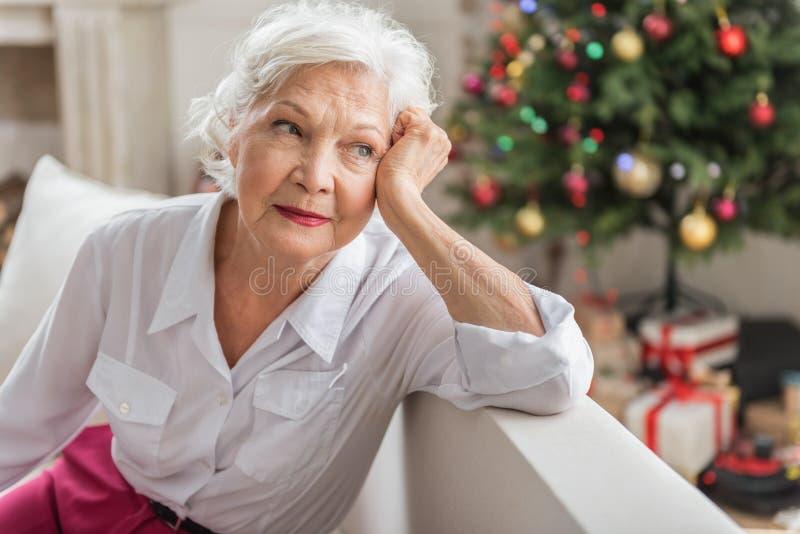 Reizend traurige alte Frau sitzt auf Sofa stockfotografie