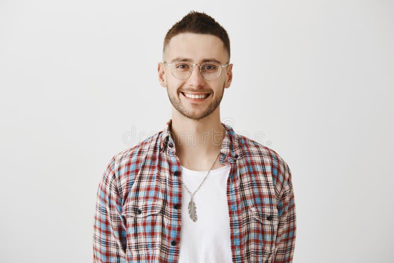 Reizend Verkäufer bereit, seinem Hilfe anzubieten Porträt des attraktiven emotionalen jungen Mannes mit Bart beim Eyewearlächeln lizenzfreie stockfotografie