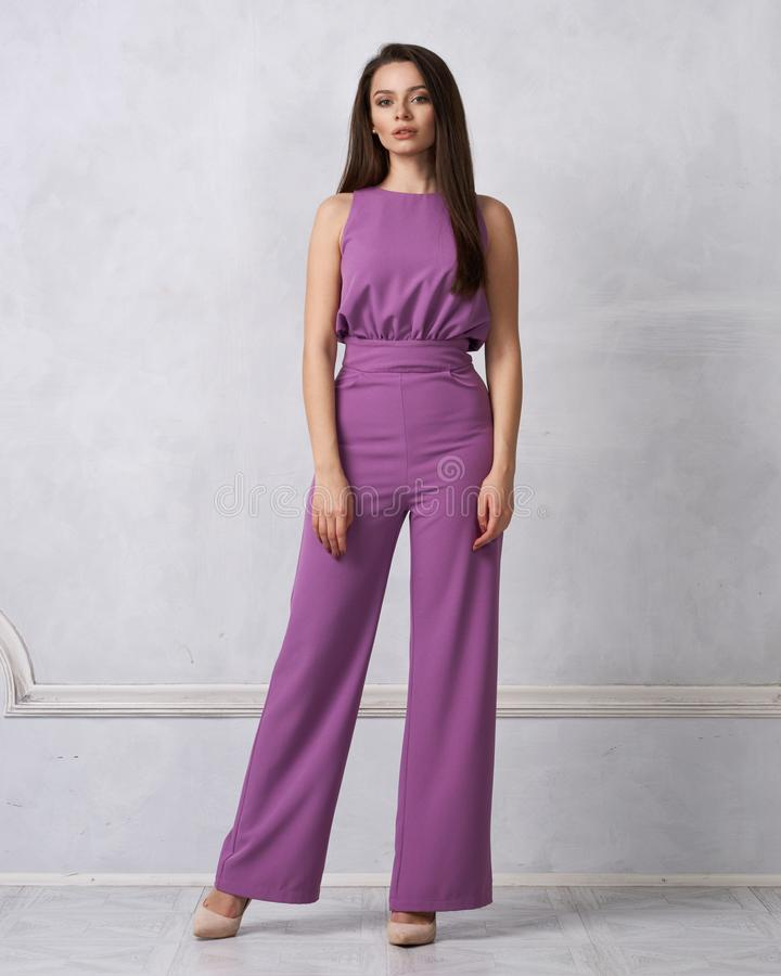 Reizend weibliches Modell im purpurroten Overall stockbild