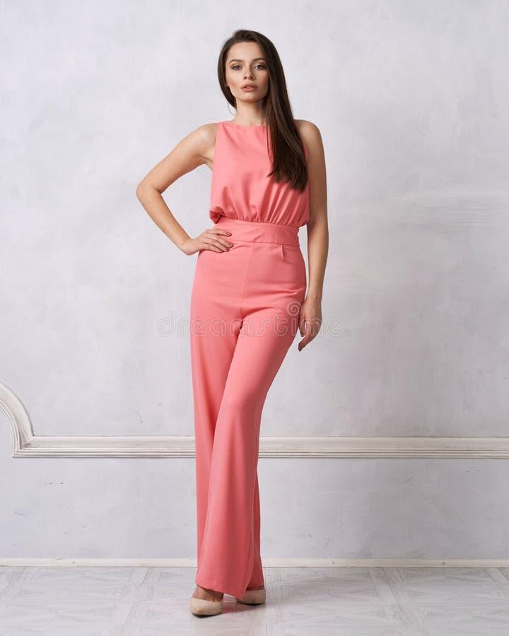Reizend weibliches Modell im rosa Overall lizenzfreie stockbilder