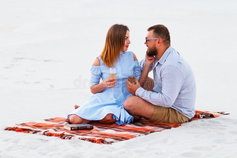 Reizende attraktive Paare, die zusammen auf dem weißen Sandstrand sitzen, Paare mit Wein oder Champagner während des romantischen lizenzfreie stockfotos