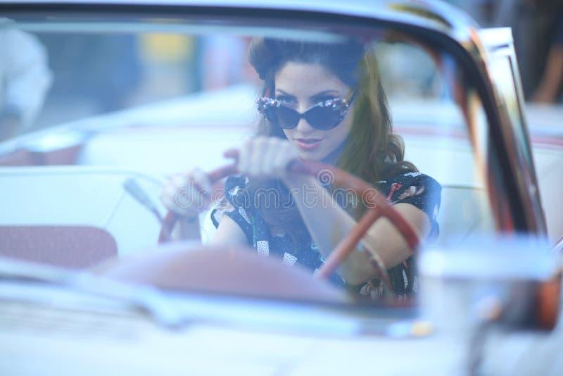 Reizende aufwerfende Frau und und um ein Weinlese-Auto stockfotos