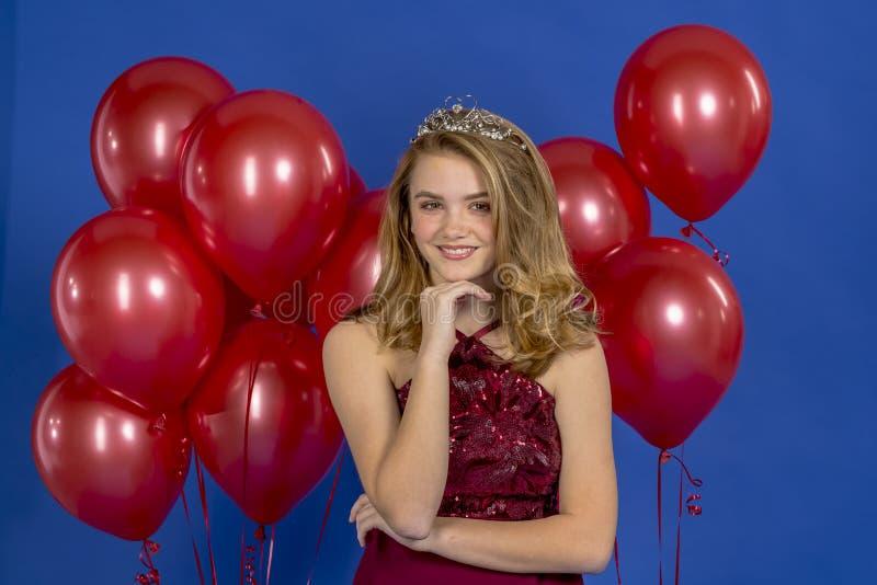 Reizende blonde Jugendstudio-Umwelt modell-Posing In-A Kleider-und Tiara Against Red Balloons Insa lizenzfreie stockfotos