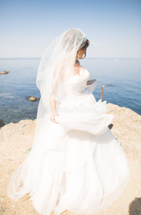 Reizende Braut im weißen Hochzeitskleid, das nahe dem Meer mit schönem Hintergrund aufwirft lizenzfreie stockfotos