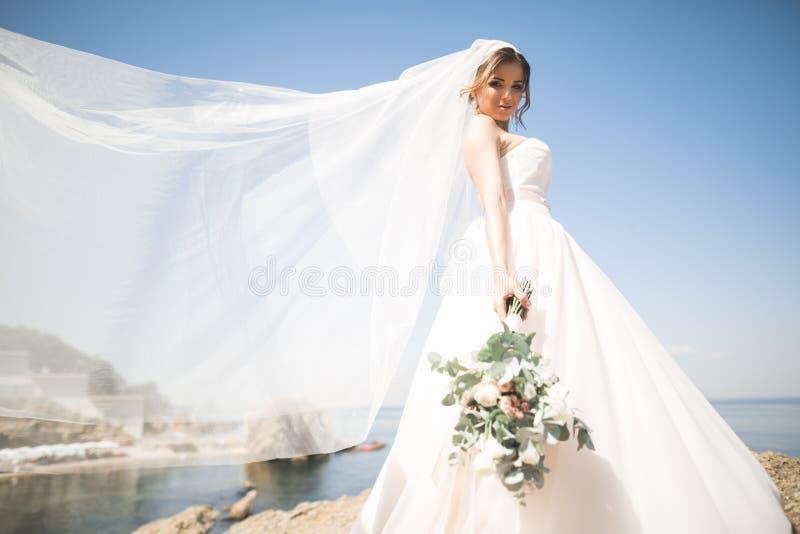 Reizende Braut im weißen Hochzeitskleid, das nahe dem Meer mit schönem Hintergrund aufwirft lizenzfreie stockbilder