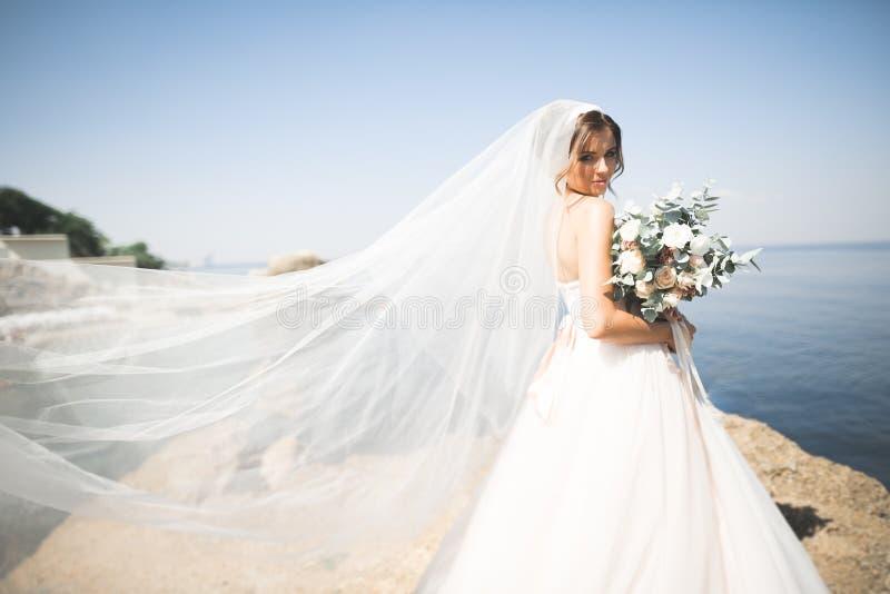 Reizende Braut im weißen Hochzeitskleid, das nahe dem Meer mit schönem Hintergrund aufwirft lizenzfreie stockfotografie