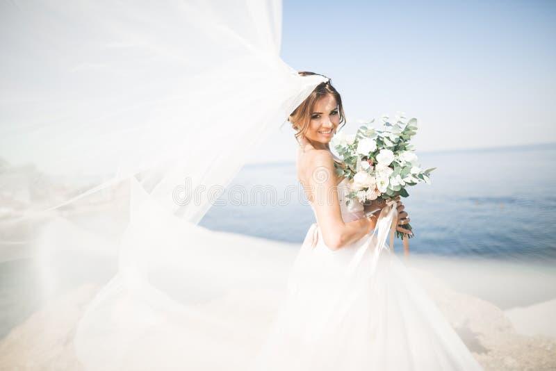 Reizende Braut im weißen Hochzeitskleid, das nahe dem Meer mit schönem Hintergrund aufwirft stockfoto