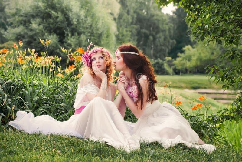 Reizende Brautjungfern, die auf dem Gras sitzen stockfotos
