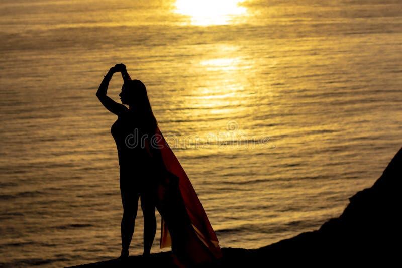 Reizende Brunette Bikini-Modell-Relaxing On The-Küstenlinie bei Sonnenuntergang stockbilder