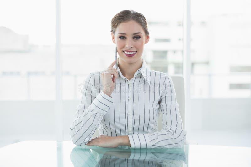 Reizende denkende Geschäftsfrau, die an ihrem Schreibtisch lächelt an der Kamera sitzt stockbilder